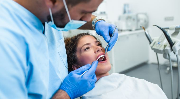 dentist examining teeth of female patient