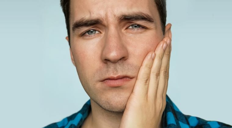 man touching his jaw and looking uncomfortable due to a toothache