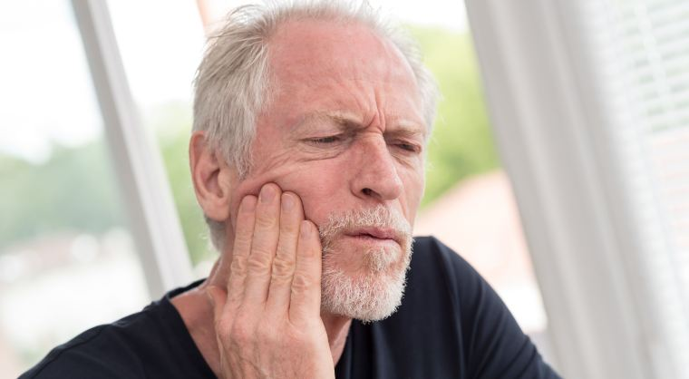 man holding his mouth due to toothache