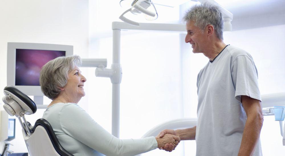 Dentist shaking patient's hand