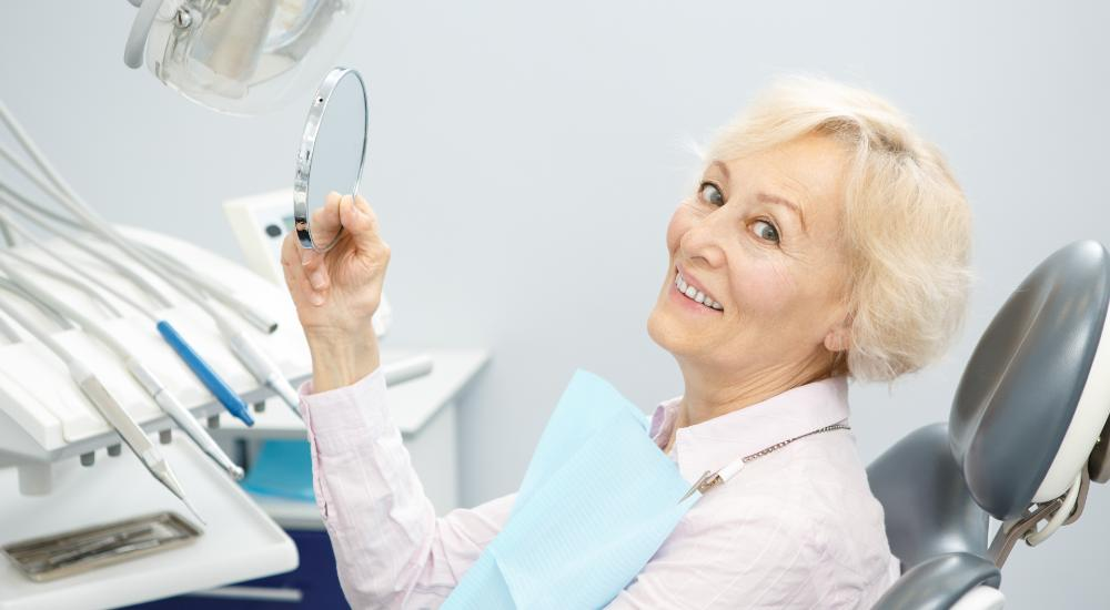 older female patient sitting in dental chair holding a mirror smiling to camera