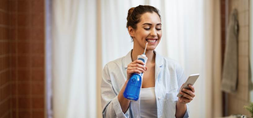 Woman holding her phone and water flosser