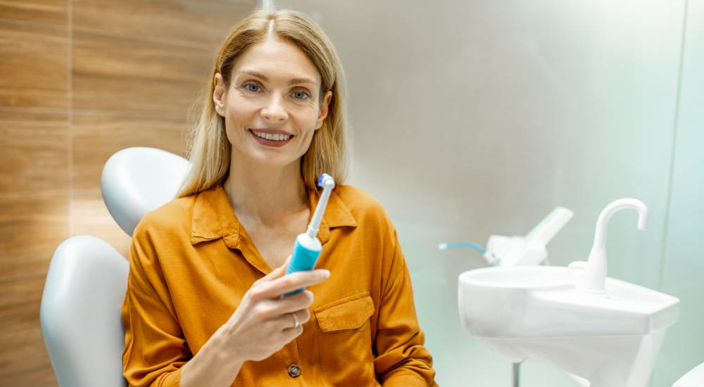Woman holding electric toothbrush