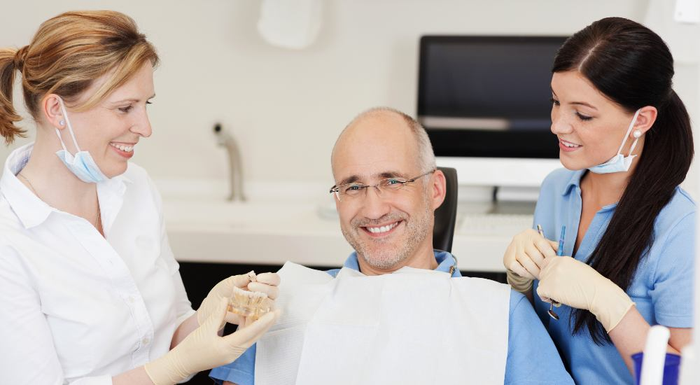 man smiling and sitting in dentist chair beside dentists following dental treatment