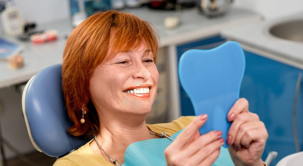 woman smiling and sitting in dentist chair looking in a mirror after getting dental implants