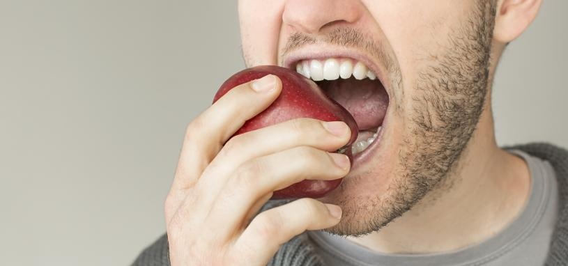 young man about to eat an apple